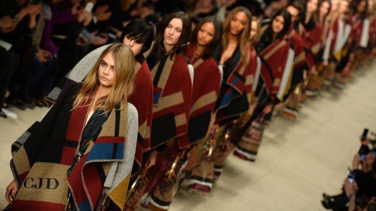 Models, led by Cara Delevingne (L) prese